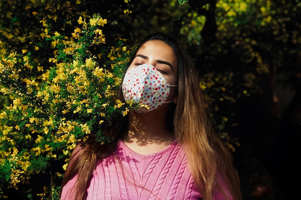 Girl in a pink jumper and wearing a face mask standing next to yellow flowers