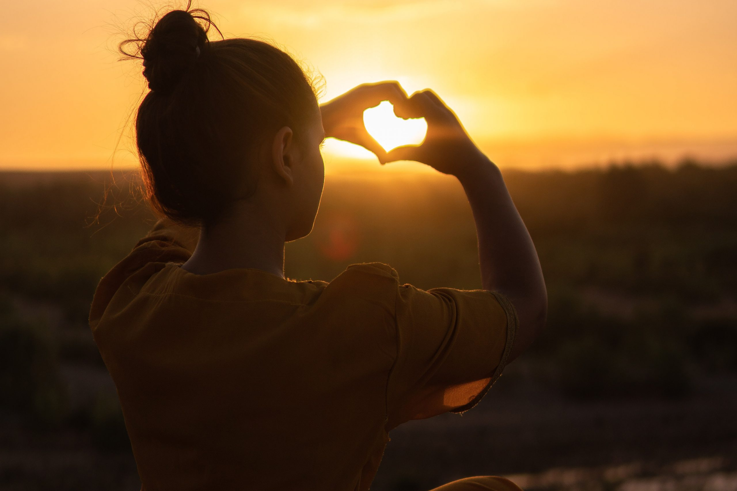 Girl making a heart shape with her hands in front of a sunset