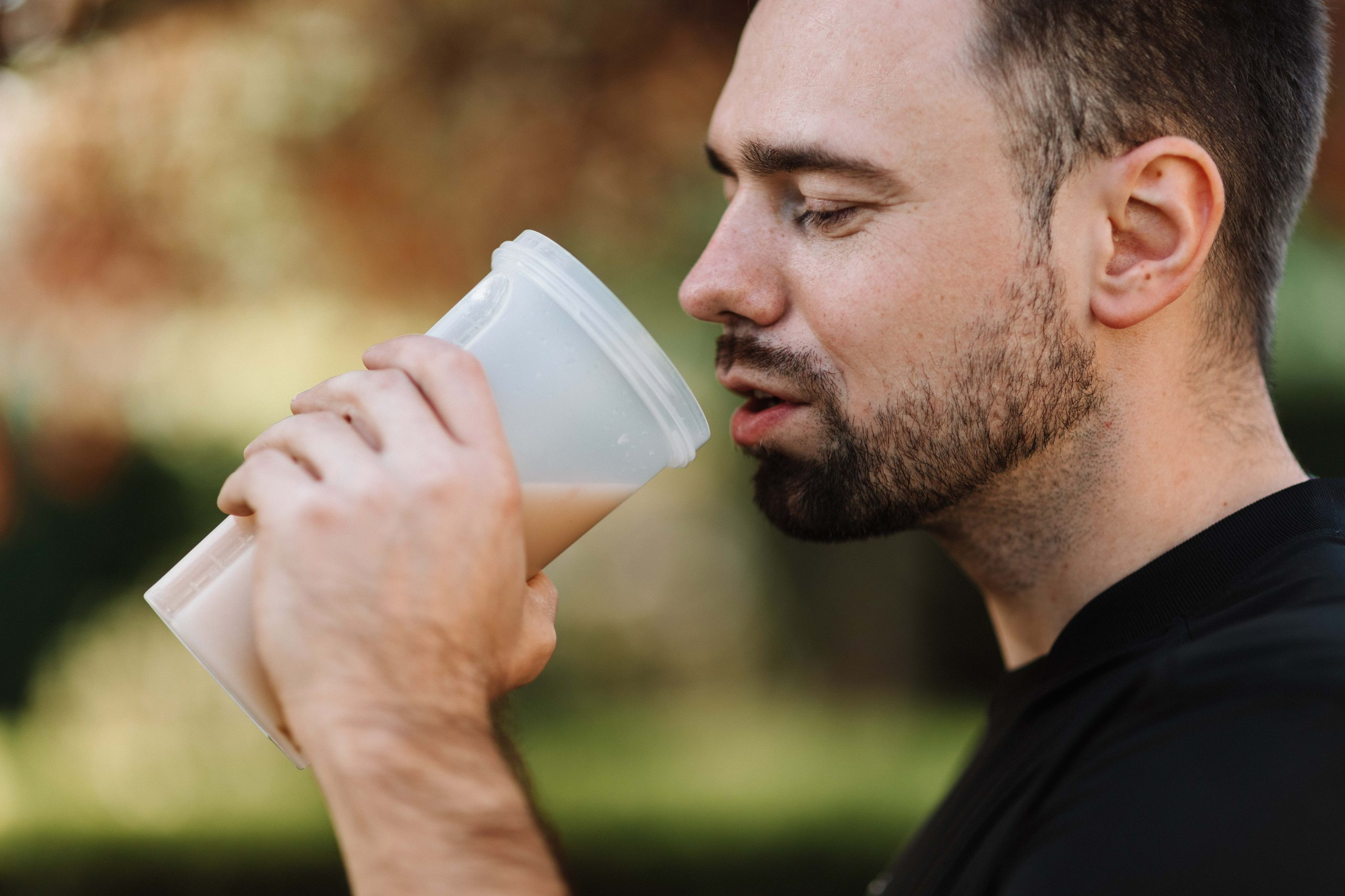 Side view of a man drinking a protein shake