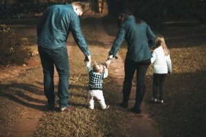 Family with two parents and two children walking on a dirt road