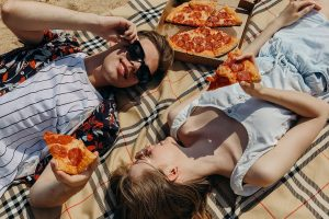 couple lying on beach with pizza