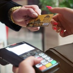 Close image of a credit card being passed from a man in a suit to a lady with bright pink nail polish to scan on an EFTPOS machine.