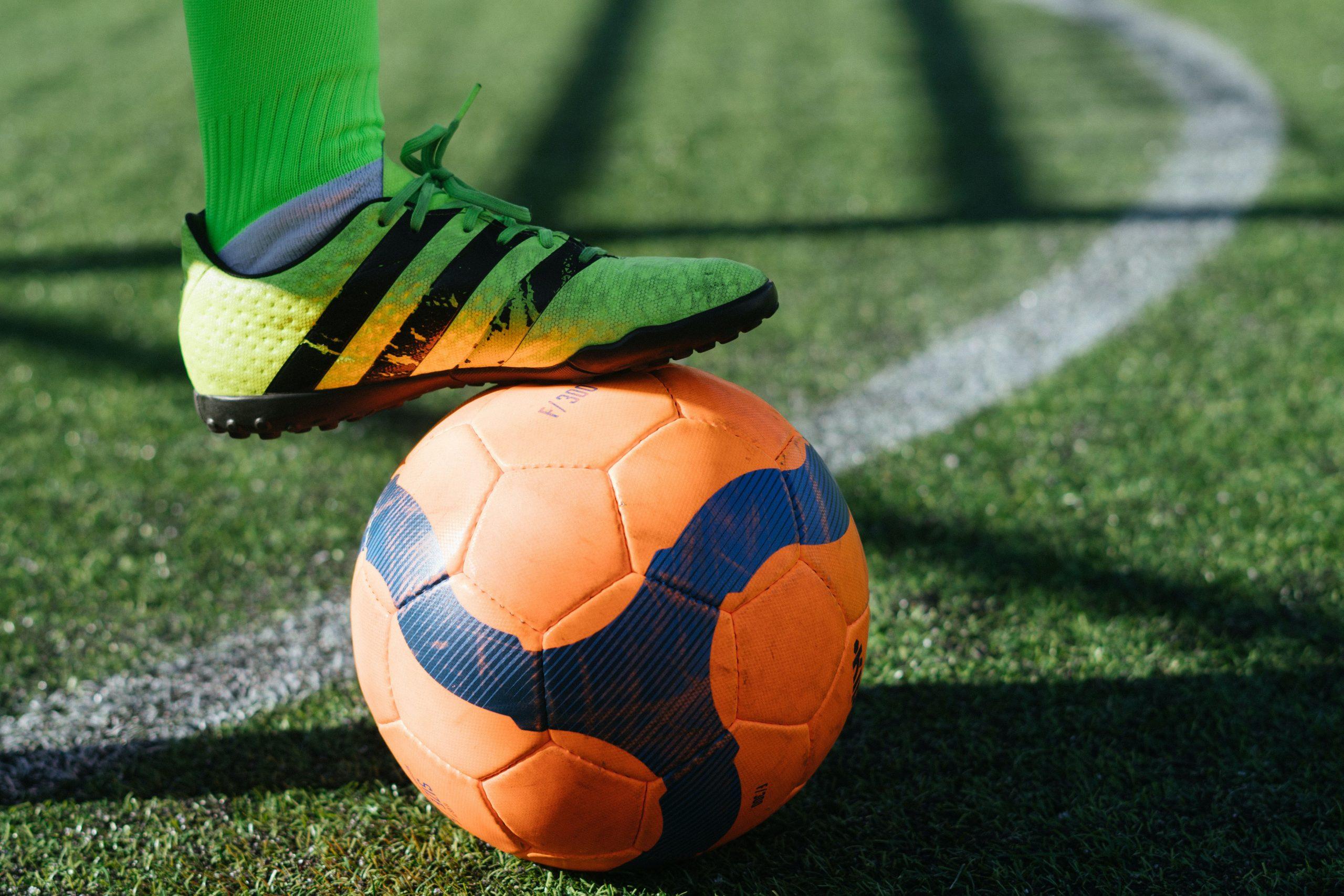 A yellow boot standing on an orange soccer ball