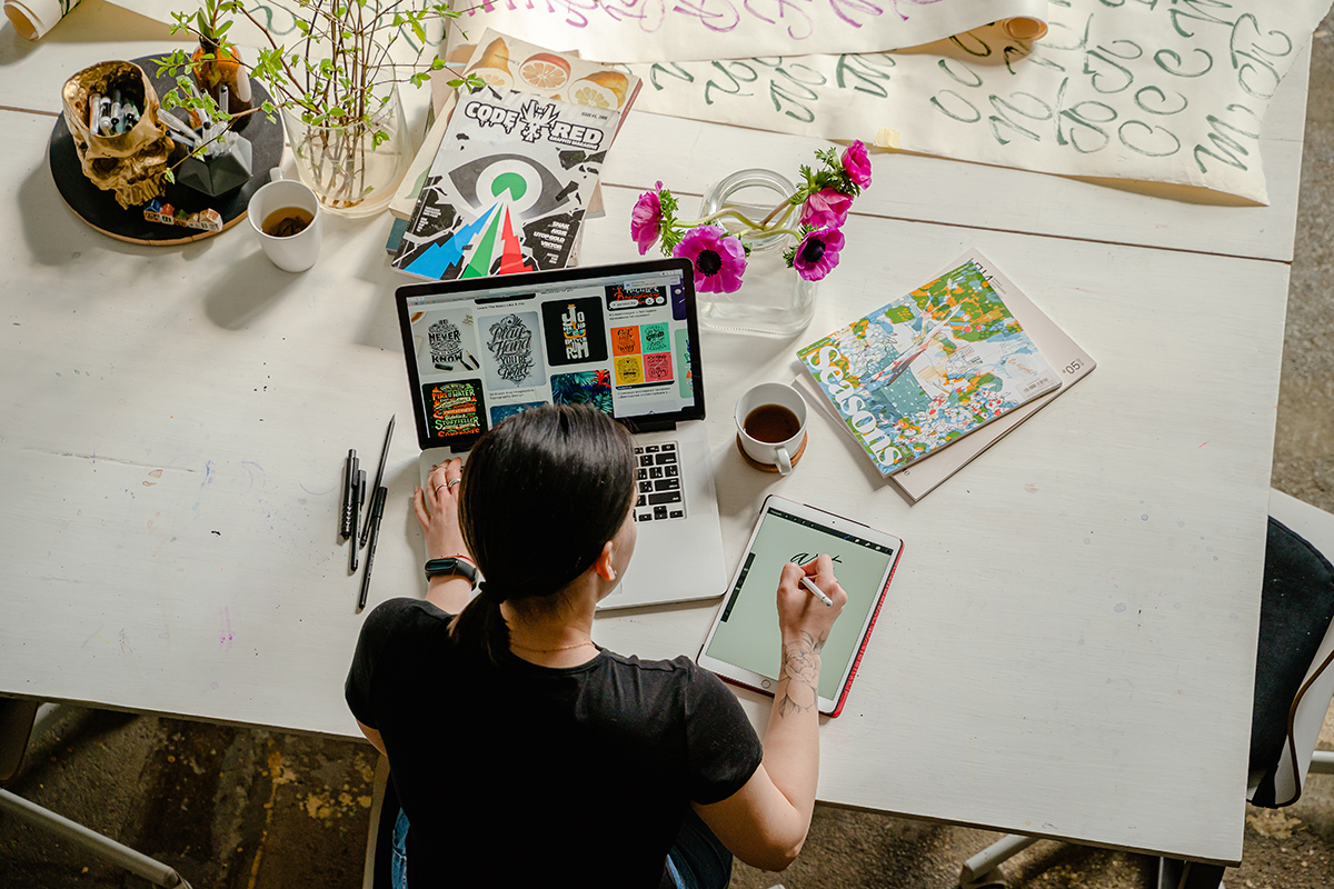 Bird's eye view of a woman sitting at a desk in front of a laptop and drawing on a tablet.