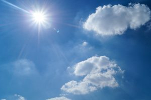 View of the sun shining in a blue sky with some clouds
