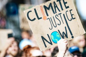 Crowd gathered outside with sign reading 'climate justice now'